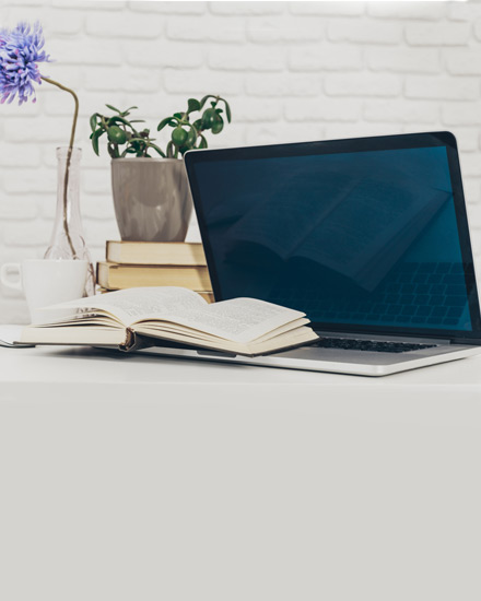 An open laptop resting on a table against a white brick wall.