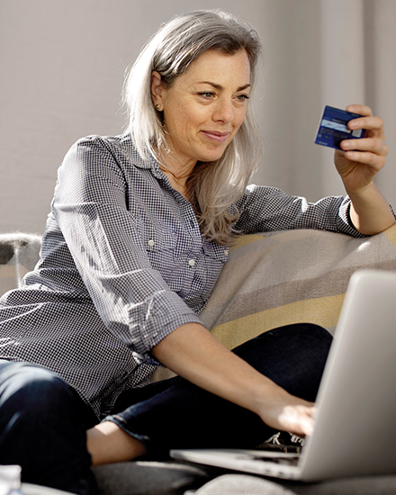A woman is sitting on a couch and using her credit card to pay a bill on her laptop.