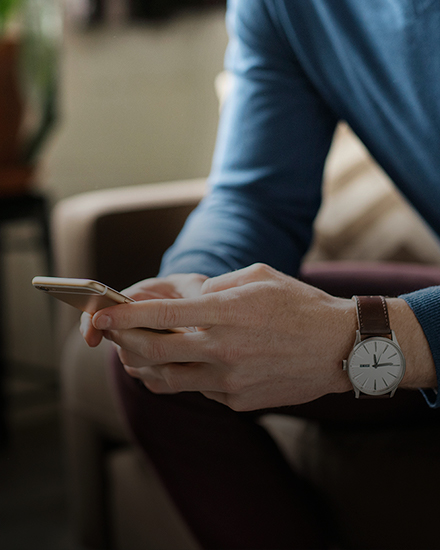 A person is sitting on a couch holding a smart phone in both hands.