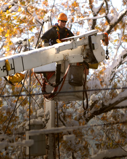 An Orange and Rockland employee in a bucket truck, with tree branches in the background.