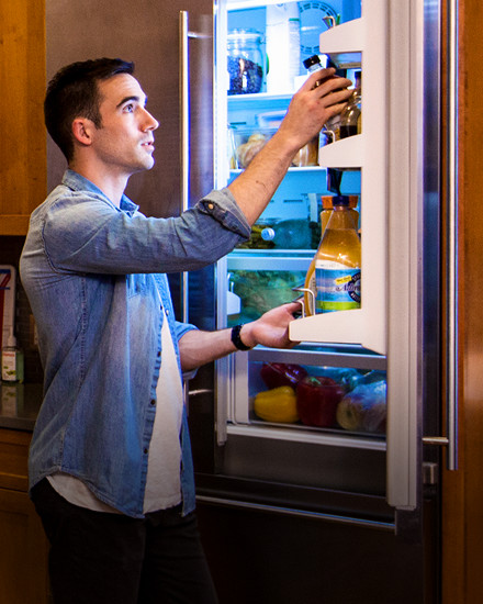 A man standing in front of an open refrigerator.