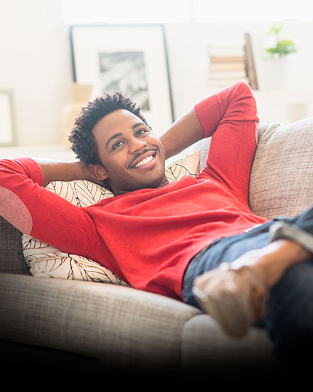 man laying on couch smiling