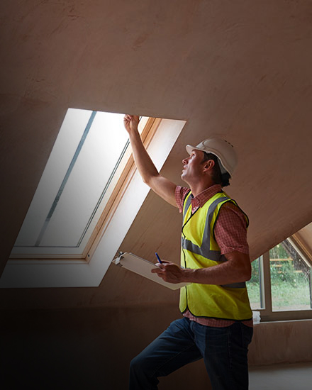 A contractor inspects a window.