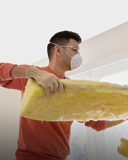 contractor installing insulation in a home