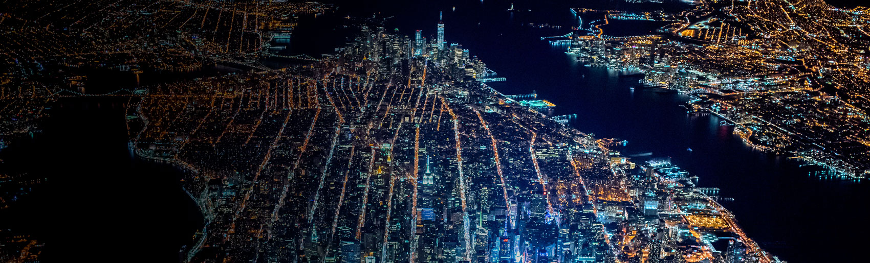An aerial view of the Manhattan city grid and Jersey shoreline, during the evening.