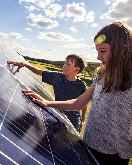 Two children examine a solar panel.
