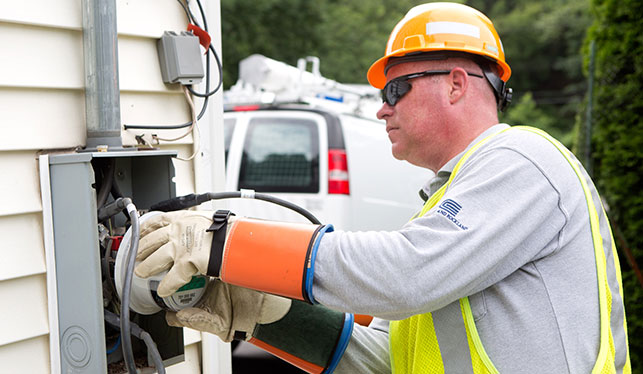 An Orange and Rockland employee is installing a smart meter on the side of a residential home.