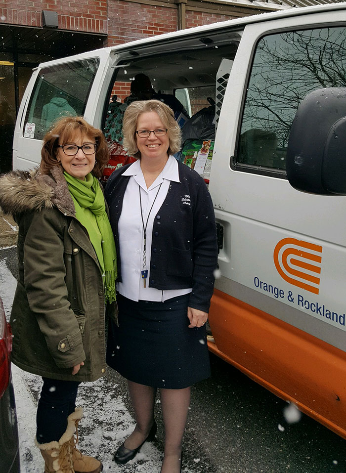 Two women in front of an O&R van filled with gifts.