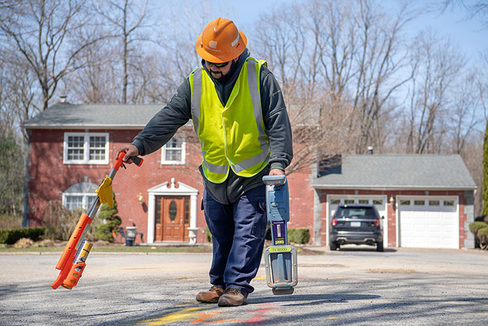 Utility worker using paint guns to mark the location of underground utility lines on a street