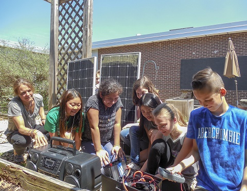 Students outdoors in school courtyard looking at a solar power station.