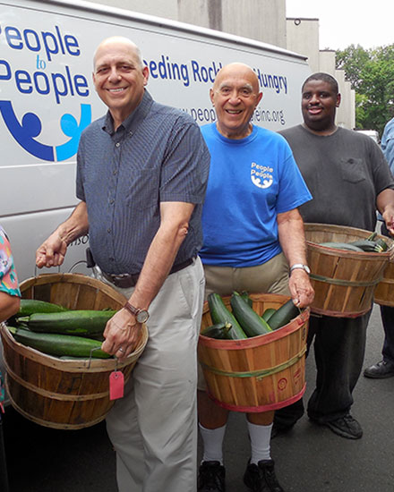 People in front of van holding vegetables to donate